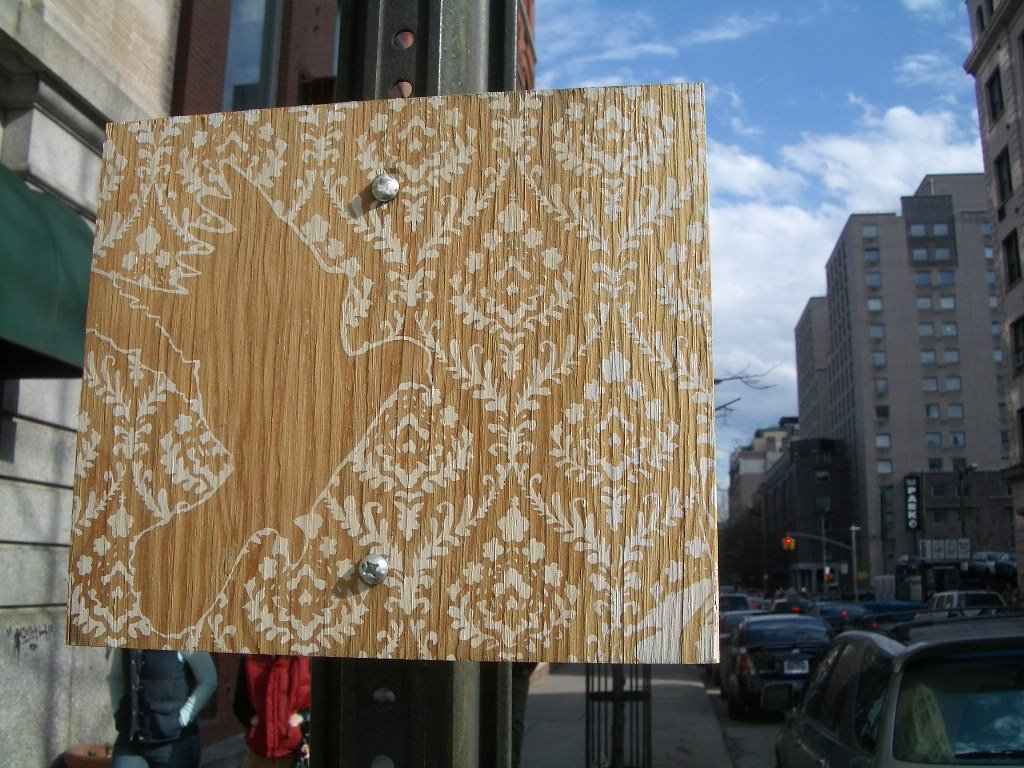 stencil graffiti painted on wood, ornate pattern oovering the surface, with a break in the shape of a flying bird